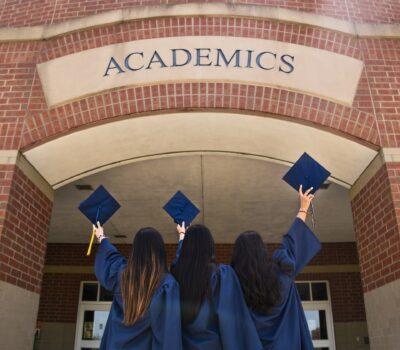 Tres mujeres con toga y birrete frente a la universidad