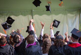 estudiantes lanzando birretes al aire